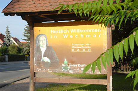 Im Bild im Kapitel Ursprung sieht man einen Touristenhinweis auf einem kleinen Plakat mit einem mit Ziegeln überdachten Konstrukt. Man sieht das Portrait von Bach und den Willkommensgruß.