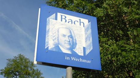 Das Foto zum Kapitel Ursprung zeigt das blaue quadratische Bach Schild wie ein Verkehrsschild, darauf steht Bach in Weimar. Rechts dahinter: grünes Baumlaub. Sonne, blauer Himmel.
