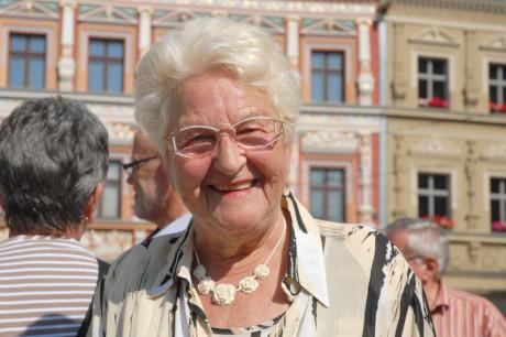 Bach Autor Helga Brück schaut lächelnd in die Kamera. Es ist ein Portrait. In Erfurt aufgenommen, mit Waidhäusern im Hintergrund.