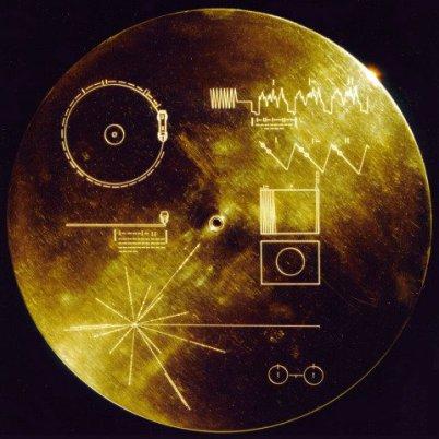 Man sieht die Golden Record = goldene Schallplatte, auf der einige schwer zu erklärende Zeichen zu sehen sind. Die Schallplatte ist auf schwarze Grund und durch das Gold der Scheibe ist ein Glanz.