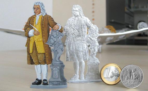 2 flache Zinnfiguren und ein Euro und ein US-Quarter sind aufgestellt. Links ist die flache Zinnfigur von Bach angemalt, in der Mitte ist sie blank, rechts sind die Münzen.