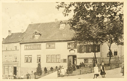 Es ist eine alte, historische Postkarte die das Bachhaus abbildet. Vorne sind zwei Mädchen zu sehen, rechts ein Baum. Alles sind blasse Brauntöne.