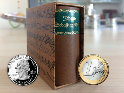 Ein winziges Buch im Schuber steht zwischen einem US-Quarter und einem Euro. Im Hintergrund ist eine Küchen-Kulisse zu sehen.