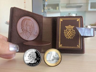 Eine Hand hält ein wnziges Bach-Buch offen. Es ist ein Lederetui, links sieht man eine winzige runde Tonplakette. Unten sieht man Euro und US-Quarter tum Vergleich.