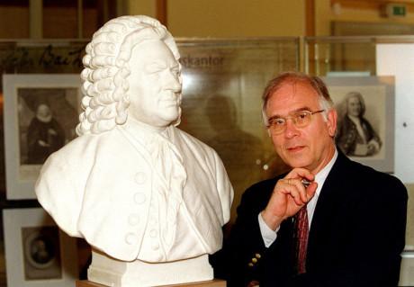 Kompetent für Bücher über Bach: Professor Wolff steht rechts im Bild, Hand am Kinn neben der Bach-Büste, die größer ist als er, es ist ein modernes Foto. Wolff ist Autor vieler Bücher zu Bach Themen.