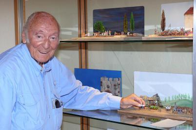 Peter Bach im blauen Hemd links präsentiert eine Zinnfigut in einem Diorama und lacht zur Kamer. Oben sieht man noch 2 Dioramen in Glasschränken.