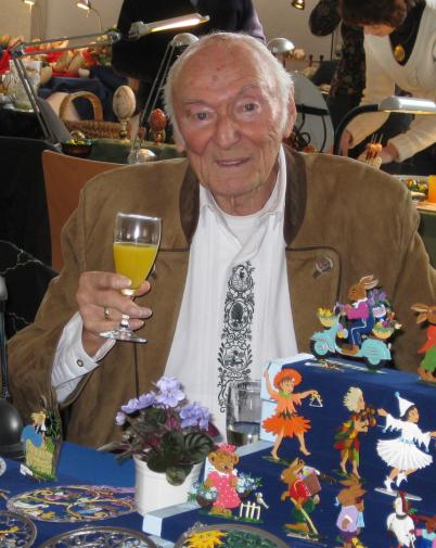 Peter Bach prostet zur Kamera. In einem Sektglas hat er Orangensaft. Er trägt ein weißes Hemd und eine hellbraune Trachtenjacke. Er sitzt hinter einem Tisch mit Zinnfiguren. Alles ist sehr bunt.