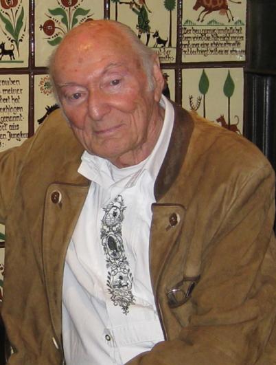 Peter Bach schmunzelt an der Kamera vorbei. Er sitzt vor einem historischen Wand-Hintergrund. Er hat ein weißes Hemd mit einer Stickerei vorne mittig an. Darüber eine hellbraune Ledertrachtenjacke.