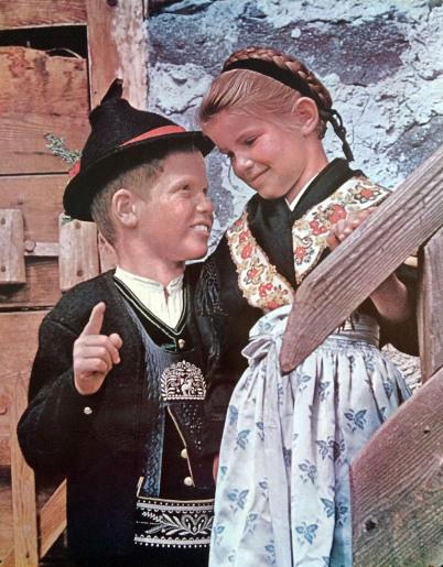 Peter Bach fotografierte dieses historische Bild von 2 Kindern in Tracht. Das Mädchen steht weiter oben hinter dem hölzernen Treppengeländer, der Junge zeigt mit dem Zeigefinger.