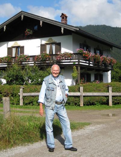 Peter Bach steht vor einem oberbayerischen Haus und lacht in die Kamera. Man sieht ihn komplett in der unteren Bildhälfte. Er hat seine geliebte Jeans und seine Jeans-Weste an. Eine Hand hat er in der Hosentasche.