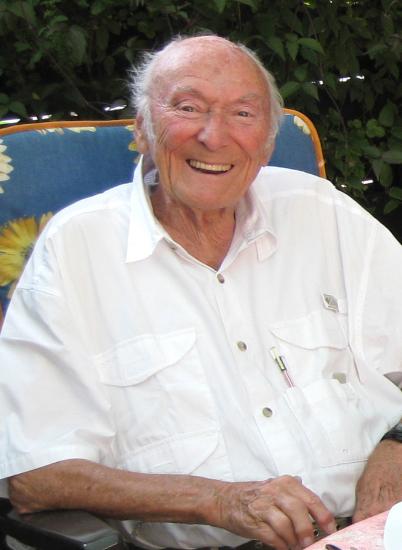 Peter Bach lacht fröhlich in die Kamera. Er sitzt auf einem Gartenstuhl im Garten. Vom Hintergrund sieht man fast nichts. Er trägt ein weißes, kurzärmeliges Hemd.