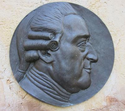 Das seitliche Portrait von Wilhelm Friedemann Bach als Metallplakette auf einer Stele in Berlin. Die Plakette ist rund und dreidimensional. Man sieht WFB in jüngeren Jahren mit Perücke ohne Band. Die Darstellung reicht bis gewirkten Hemdkragen.
