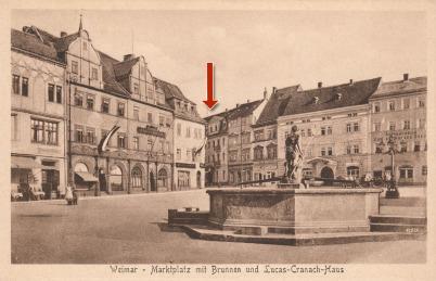Man sieht eine braunstichige historische Postkarte mit dem Marktplatz in Weimar. Im Vordergrund ist ein Brunnen, im Hintergrund sieht man zwei Häuserzeilen. Ein Haus ist mit einem roten Pfeil hervorgehoben, es ist das Geburtshaus von Wilhelm Friedemann Ba