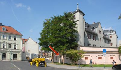 In der Nähe der Wilhelm-Friedemann-Bach-Gedenktafel blickt man auf das Rote Schloss in Weimar in der rechten Bildhälfte. Es ist ein modernes Foto. In der Bildmitte ist eine gelbe Kutsche, Ein roter Pfeil deutet auf das JSB-Denkmal zwischen 2 Bäumen.