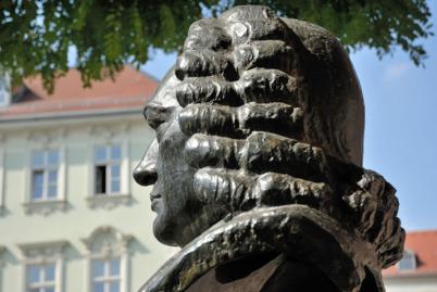 Ein Denkmal des Vaters von Wilhelm Friedemann Bach: Es zeigt den Kopf des Johann Sebastian Bach seitlich von der Rückseite. Die Perücke dominiert. Im Hintergrund ein gelbliches historisches Gebäude, oben ist Baumlaub. Der Himmel ist wolkenlos blau.