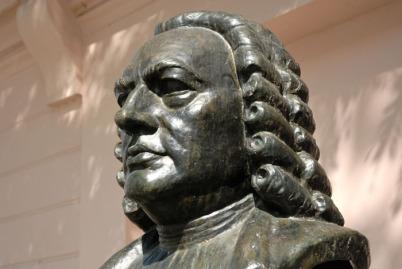 Man sieht - in einem modernen Foto - den Vater von Wilhelm Friedemann Bach bis zur Schulter. Es ist aus Bronze, Johann Sebastian Bach ist in mittlerem Alter. Dahinter ist eine hell Hauswand.