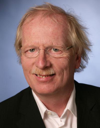 Wilhelm-Friedemann-Bach-Buchautor Dr. Ulrich Kahmann schaut zur Kamera und lächelt zum Betrachter. Er trägt eine randlose Brille, ein weißes Hemd und ein dunkles Jacket.