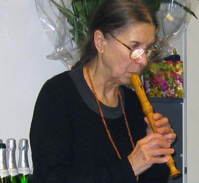 Wilhelm-Friedemann-Bach-Verehrerin Gisela Thielicke beim Flötenspiel. Sie blickt über ihre Flöte und hat einen schwarzes Kleidungsstücke an. Darüber trägt sie eine Kette. Im Hintergrund sieht man Blumen, vorne links sind Sektflaschen im Bild zu sehen.