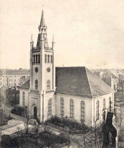 Auf einer historischen Postkarte in leichtem Gilbton ist die damalige Sebastianskirche abgebildet. Es ist eine Aufnahme von oben, es ist Winter.