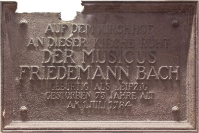 """Man sieht die erste Gedenktafel in Bronze: Sie erinnert an den """"Musicus"""" Wilhelm Friedemann Bach. Oben links ist sie beschädigt."""
