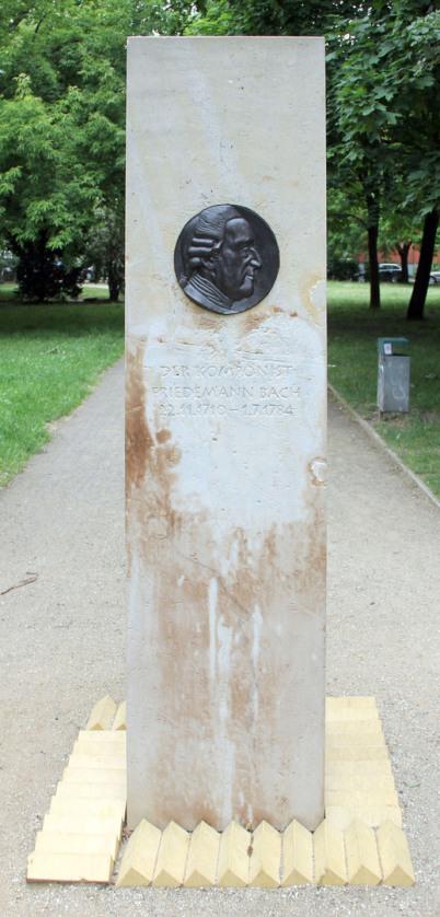 Die Wilhelm-Friedemann-Bach-Stele in ein einer Berliner Grünanlage. Man sieht die ganze etwa 4 Meter hohe Stele mit der runden Wilhelm-Friedemann-Bach-Plakette auf einem Weg vor Bäumen.