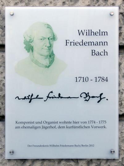 Die Wilhelm-Friedemann-Gedenktafel an einem Wohnhaus in Berlin-Mitte. Links oben ist das Portrait von WFB in einem leichten Grünton, danbenen der Schriftzur Wilhelm Friedemann Bach. DArunter sind Unterschrift und Jahreszahlen. Es ist weißes millchiges Gla