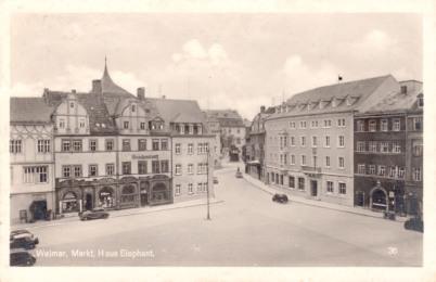 Auf einer schwarzweißen historischen Postkarte, die von oben aufgenommen ist, erkennt man das Lucas-Cranach-Haus, auf dem Weimarer Marktplatz. Im Hintergrund erkennbar ist das Wohnhaus, in welchem Wilhelm Friedemann Bach geboren wurde.