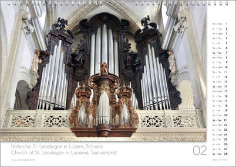 Es ist das Februarblatt in einem Orgelkalender. Die Orgel ist in Goldtönen. Im rechten Achtel ist das Kalendarium, im unteren Achtel ist der Monat sichtbar und es gibt eine zweisprachige Beschreibung vom Standort der Orgel.