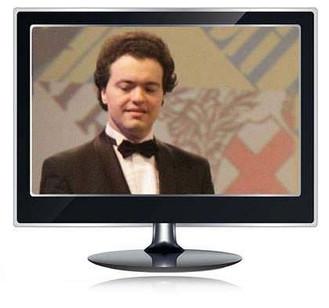 Das Bild zum Zitat zu Bach: Ein Farbfoto von Kissin. Er steht vor dem Publikum, hat die Augen geschlossen, lächelt aber. Hintergrund: ein riesiges Wappen. Das Foto ist in einem schwarzen Bildschirm.